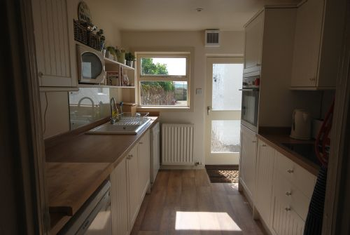 Kitchen with door leading out to back garden
