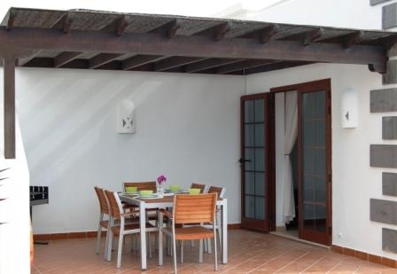 A pool side patio area providing shade from the sun and complete with quality table, six chairs and barbeque