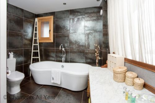 Family bathroom off the living area with stylish bath