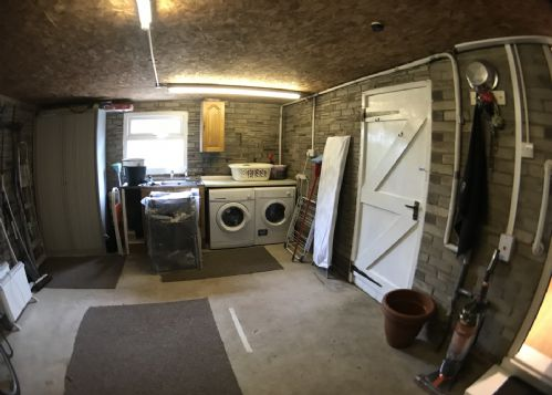 Garage with utility appliances and access to the garden