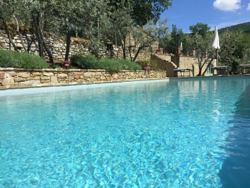 Tuscany Castello Roccolo Private Pool with villa in backgound.