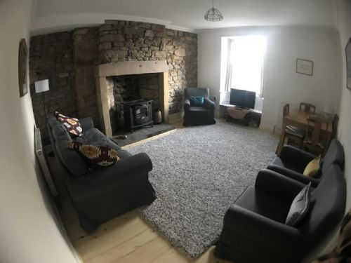 Cosy lounge / dining room with feature fireplace & electric log effect burner