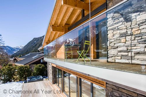 The mountains are reflected in the glass balcony