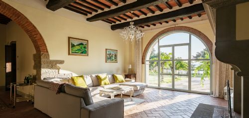 Large sitting area with large TV, Stonefireplace and entrance to gardens and pool