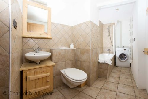 Family bathroom with washing machine and bath / shower