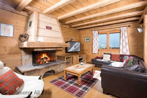 Cosy lounge area in traditional alpine chalet with log fire