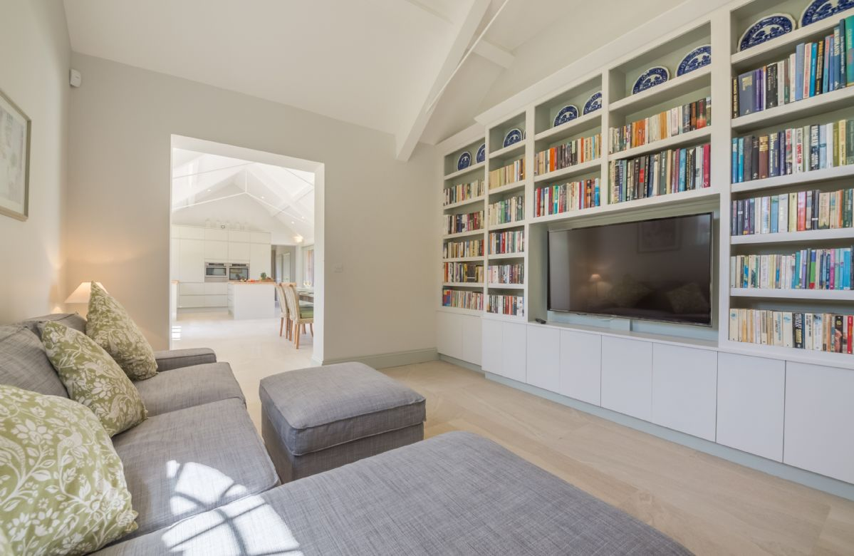 Cosy snug/TV room with fitted bookshelves and selection of books