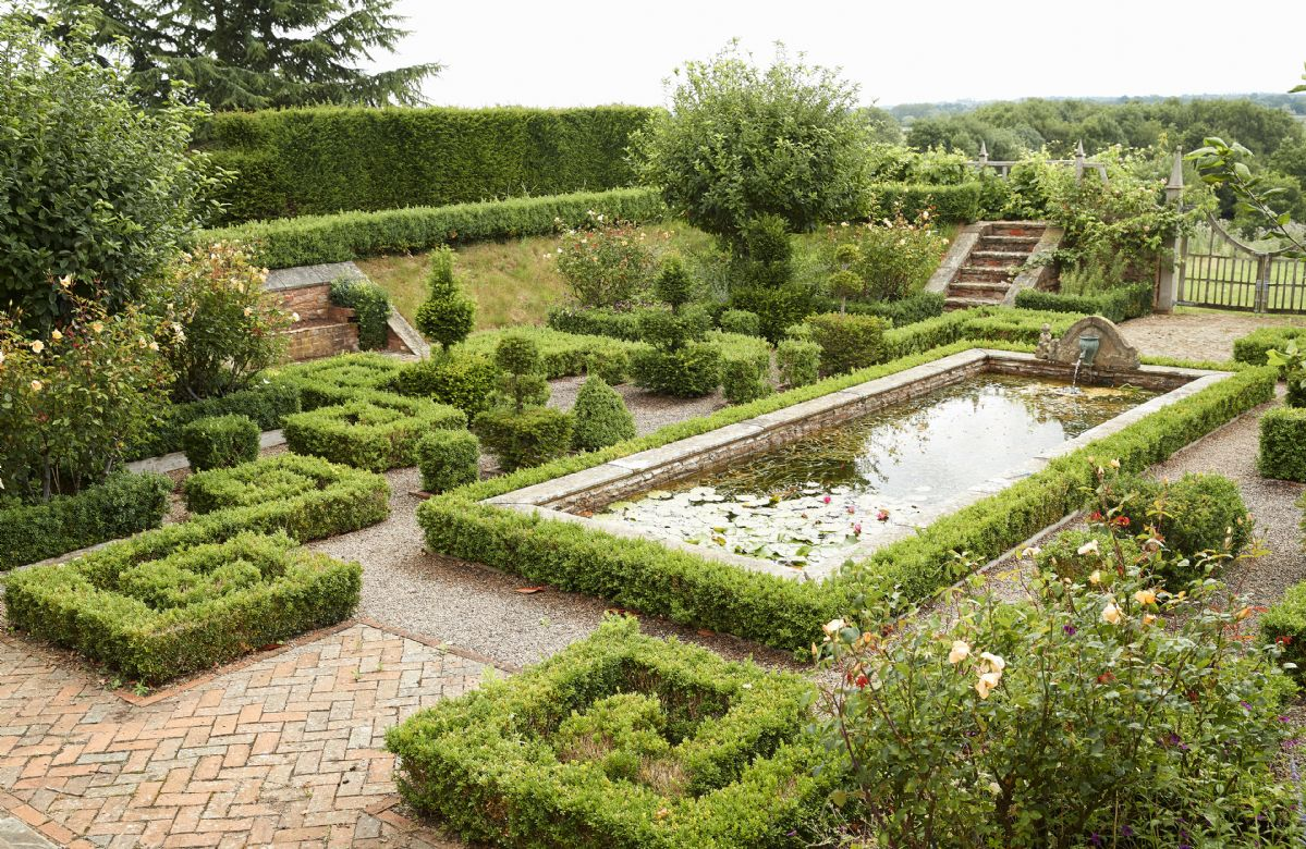 The sunken garden has an ornamental pond surrounded by beds of tulips, alliums and roses