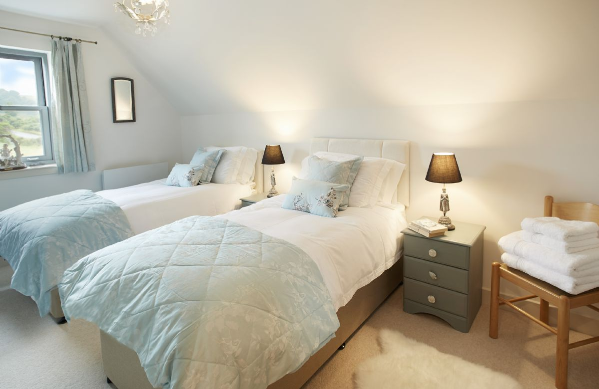 First floor: Twin bedroom with 3' single beds, a large wardrobe with storage and three windows with outstanding views