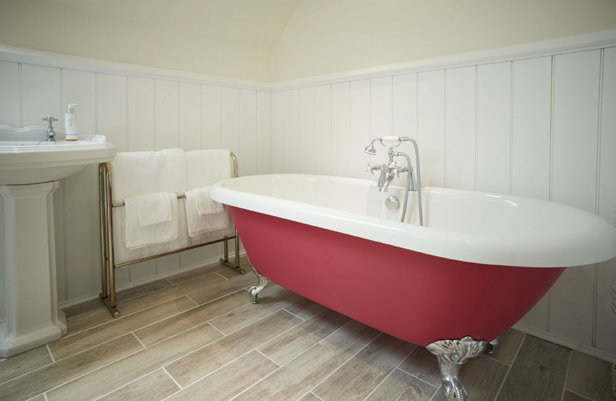 First floor: spacious family bathroom featuring underfloor heating, roll-top bath with hand-held shower facility