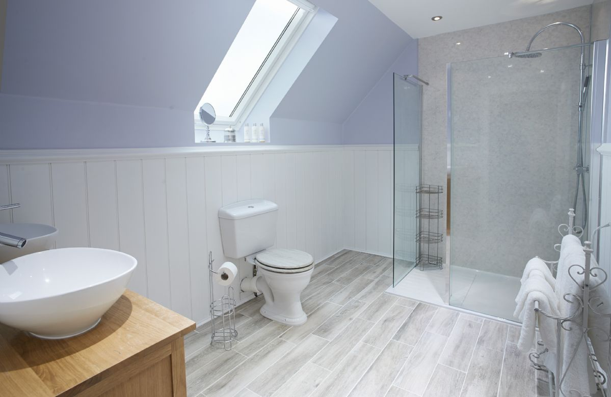 First floor: en-suite bathroom with underfloor heating, double sink unit and large walk in shower