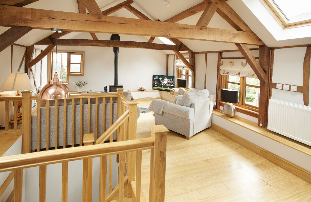 First floor:  Open plan sitting area with exposed wall beams and trusses to the full height ceiling and wood burning stove