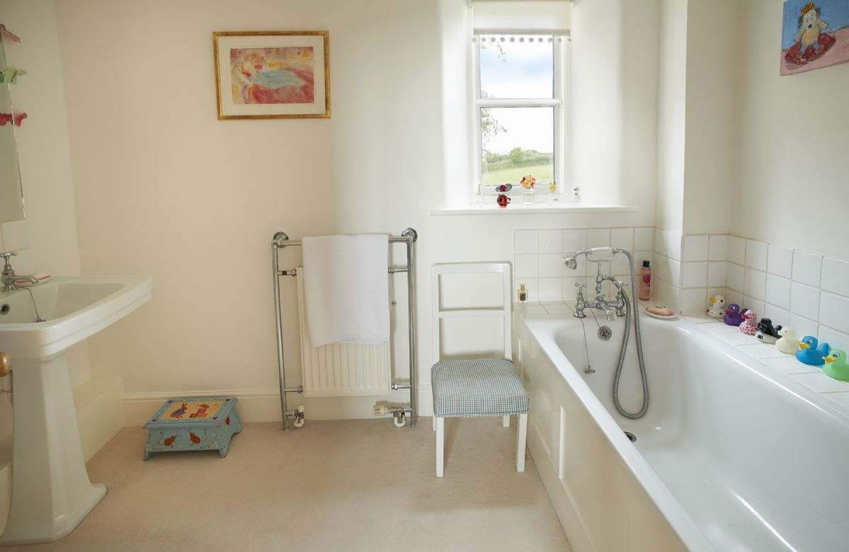 First floor: En-suite bathroom with bath and hand-held shower attachment
