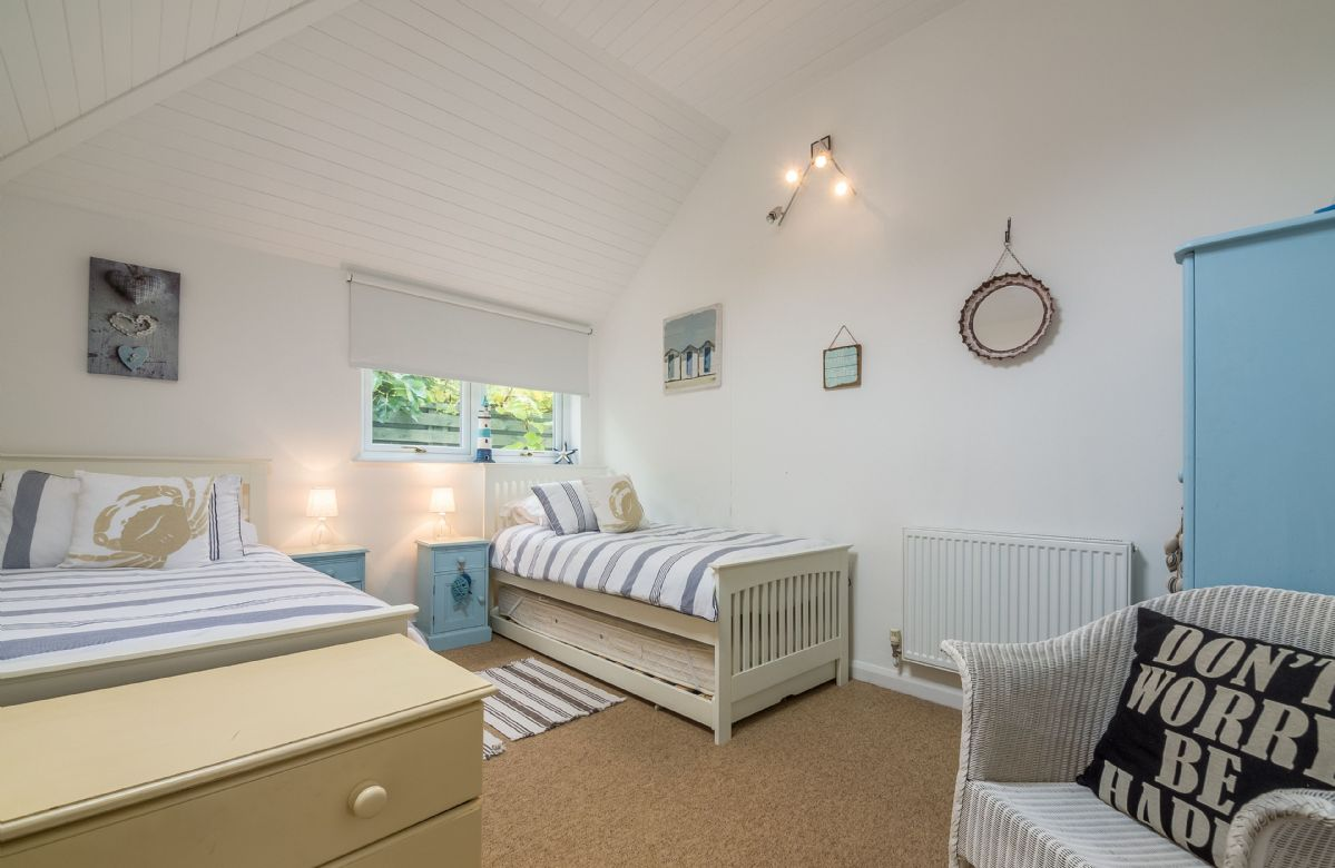 Up a step from the kitchen is a twin bedroom with 3' single beds