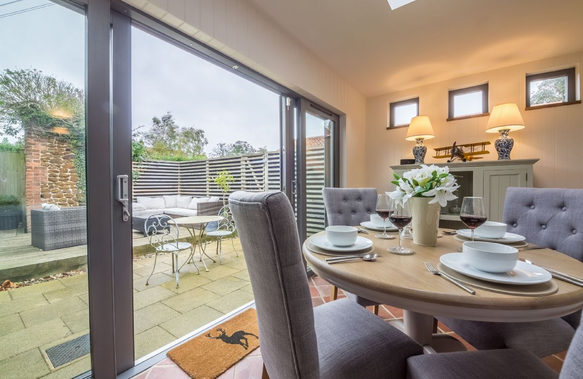 Ground floor: Garden room with dining table and chairs with french doors leading to the garden