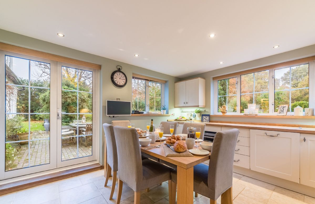 Ground floor: Kitchen with breakfast table and french doors which open onto a paved terrace