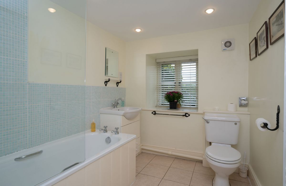 First floor: En suite bathroom with shower over the bath