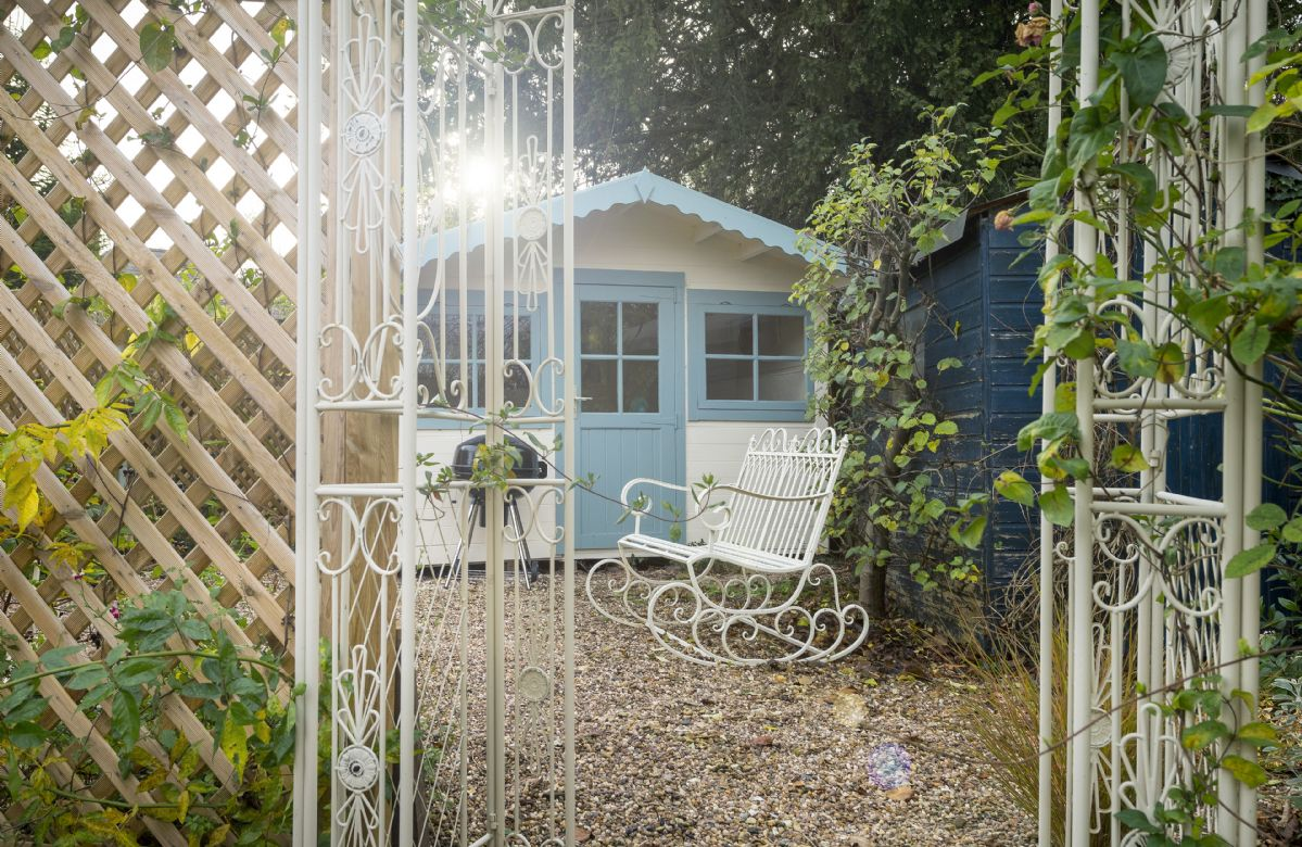The garden features a pretty summer house and charcoal barbecue, perfect for sunny days