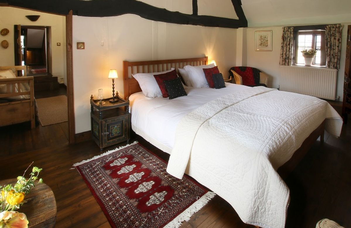 First floor: Third bedroom with a 6' super-king bed, exposed beams and an attractive cruck shaped ceiling
