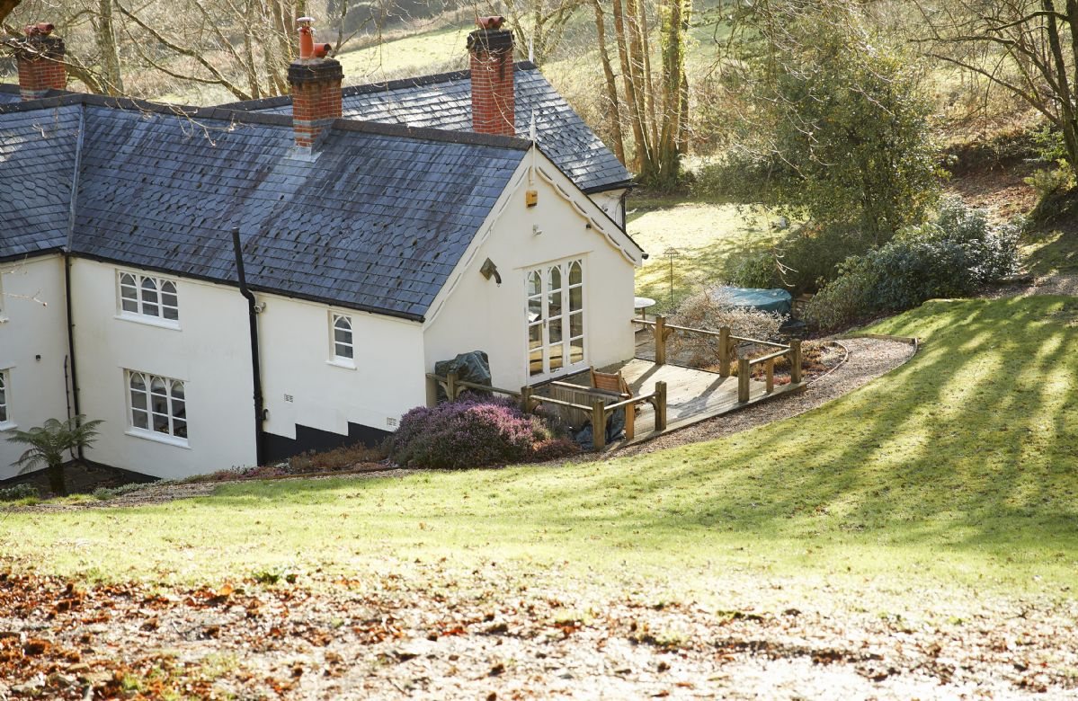 Slowpool is set into a slope with a wooden balcony and french doors which open into the first floor single bedroom