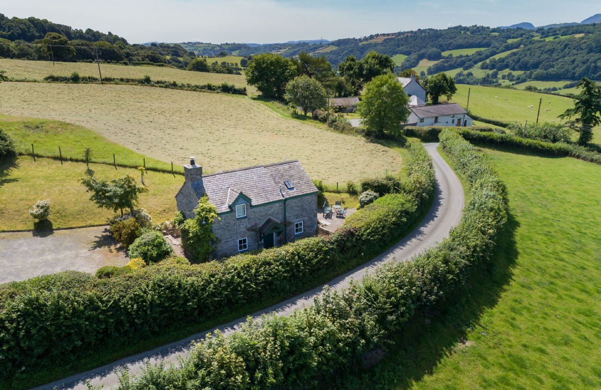 Ty Ucha'r Fforrd with enclosed garden, part of which is on a slope with a level sitting area in front of the cottage commanding the view and others behind the cottage