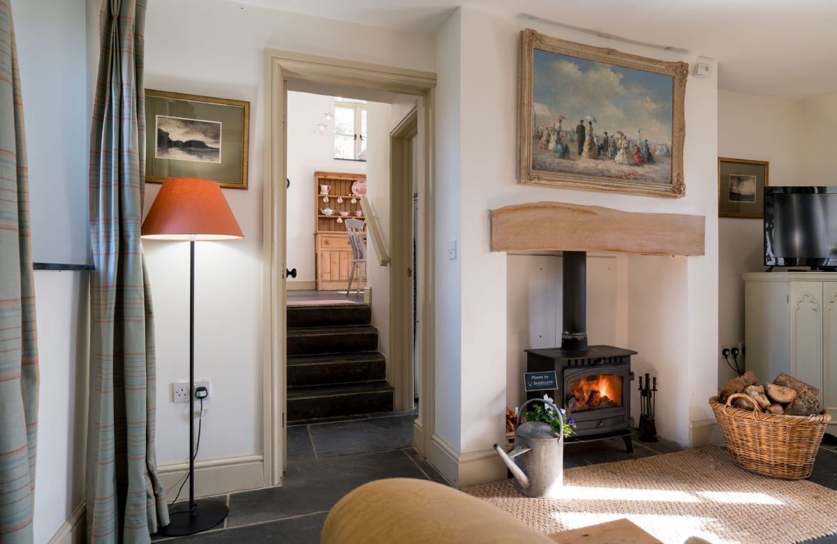 Steps lead down from the kitchen to the sitting room with woodburning stove