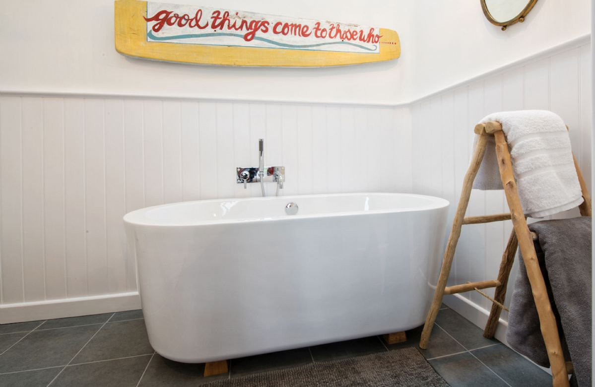 En-suite bathroom with free standing bath plus festoon lights above the bath