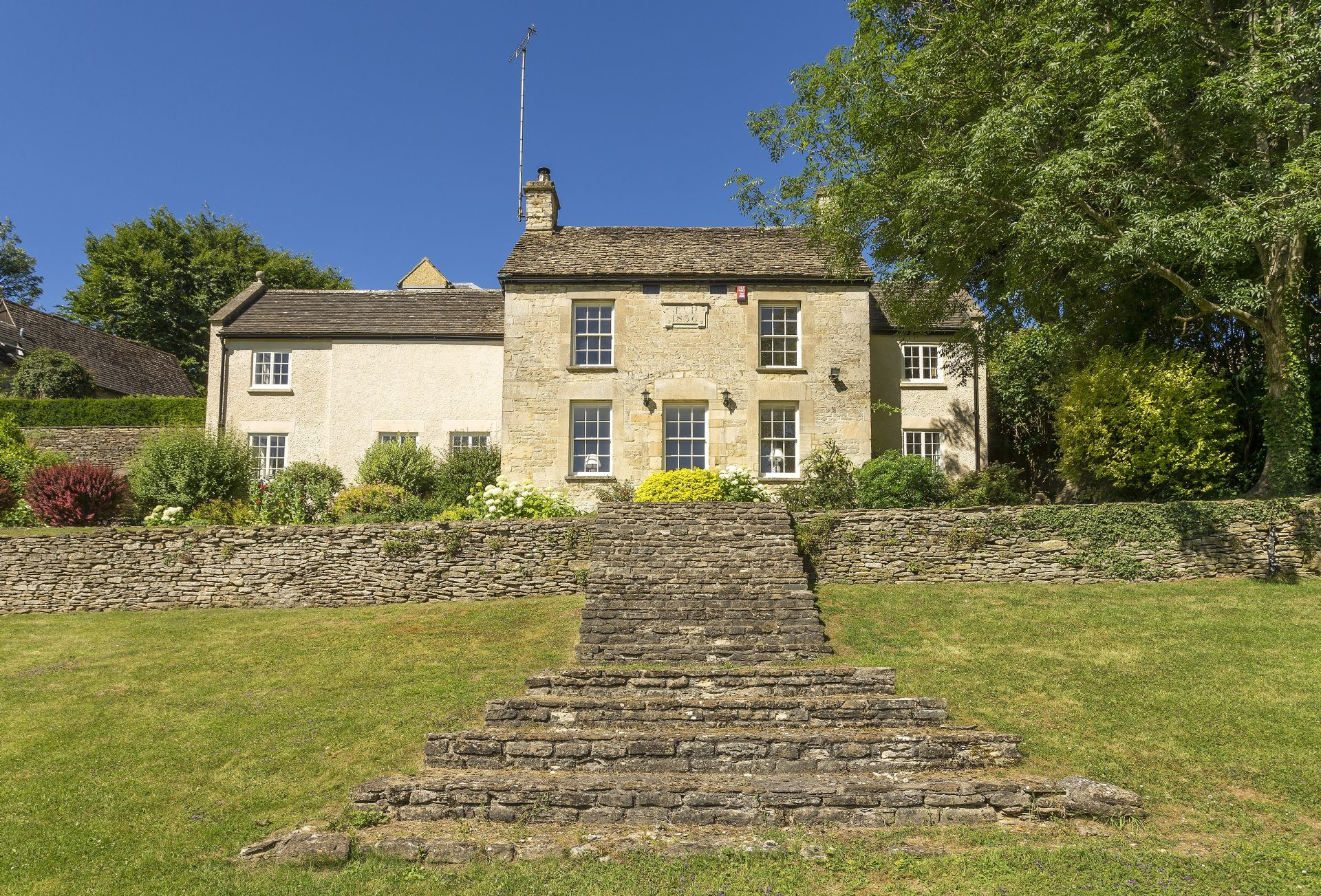 Catalpa Cottage is a detached 19th century Cotswold cottage set in a quiet corner of Tetbury yet only a three minute walk from the centre. It is set in an elevated position above a one acre private garden