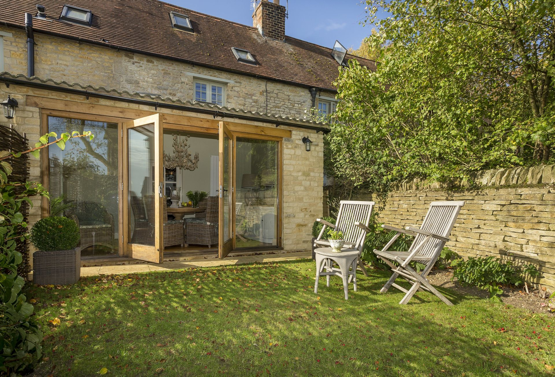 The garden room to the rear of the cottage opens onto a private patio and enclosed garden