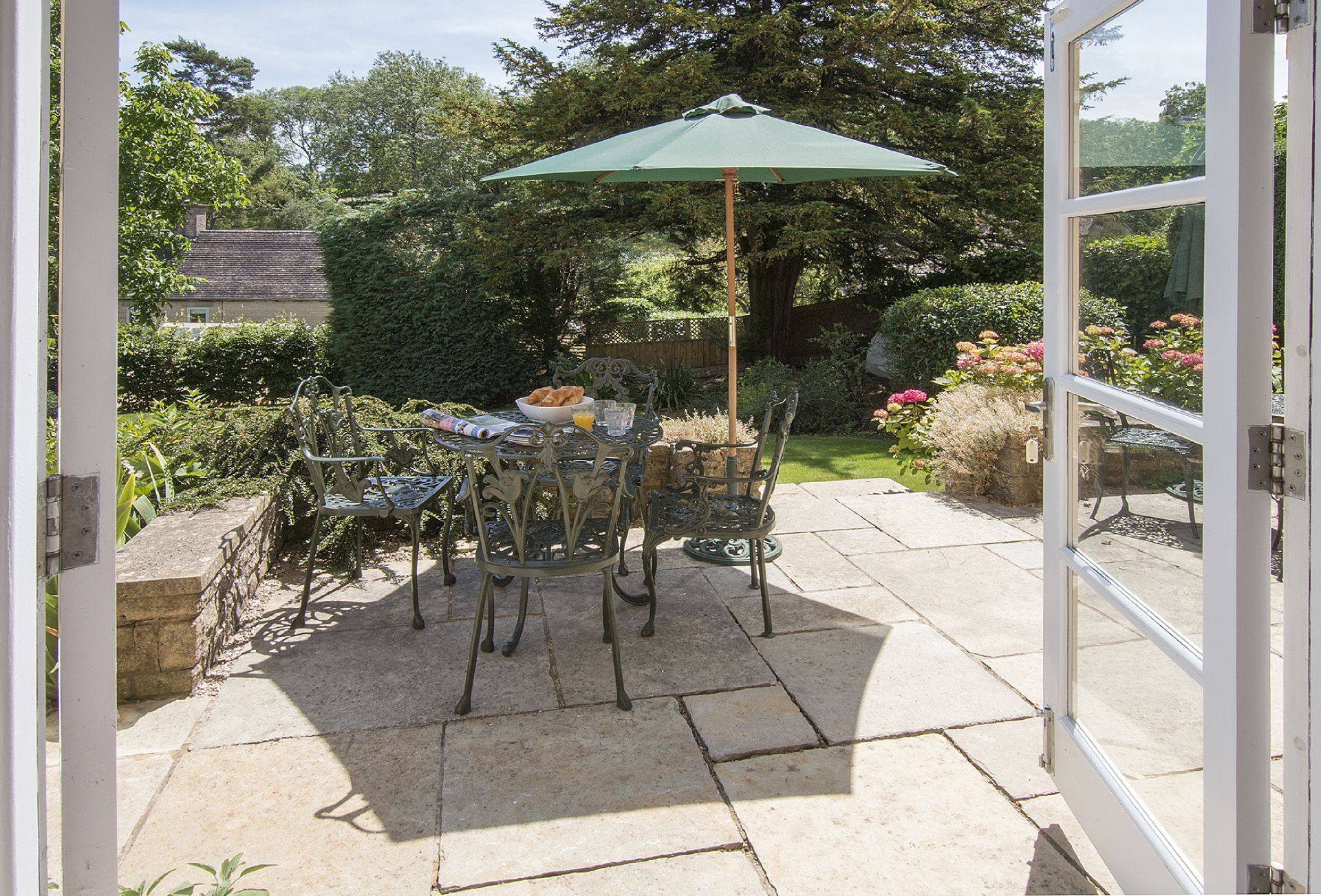 A patio area with bistro tables and chairs to seat eight. A barbecue is also available