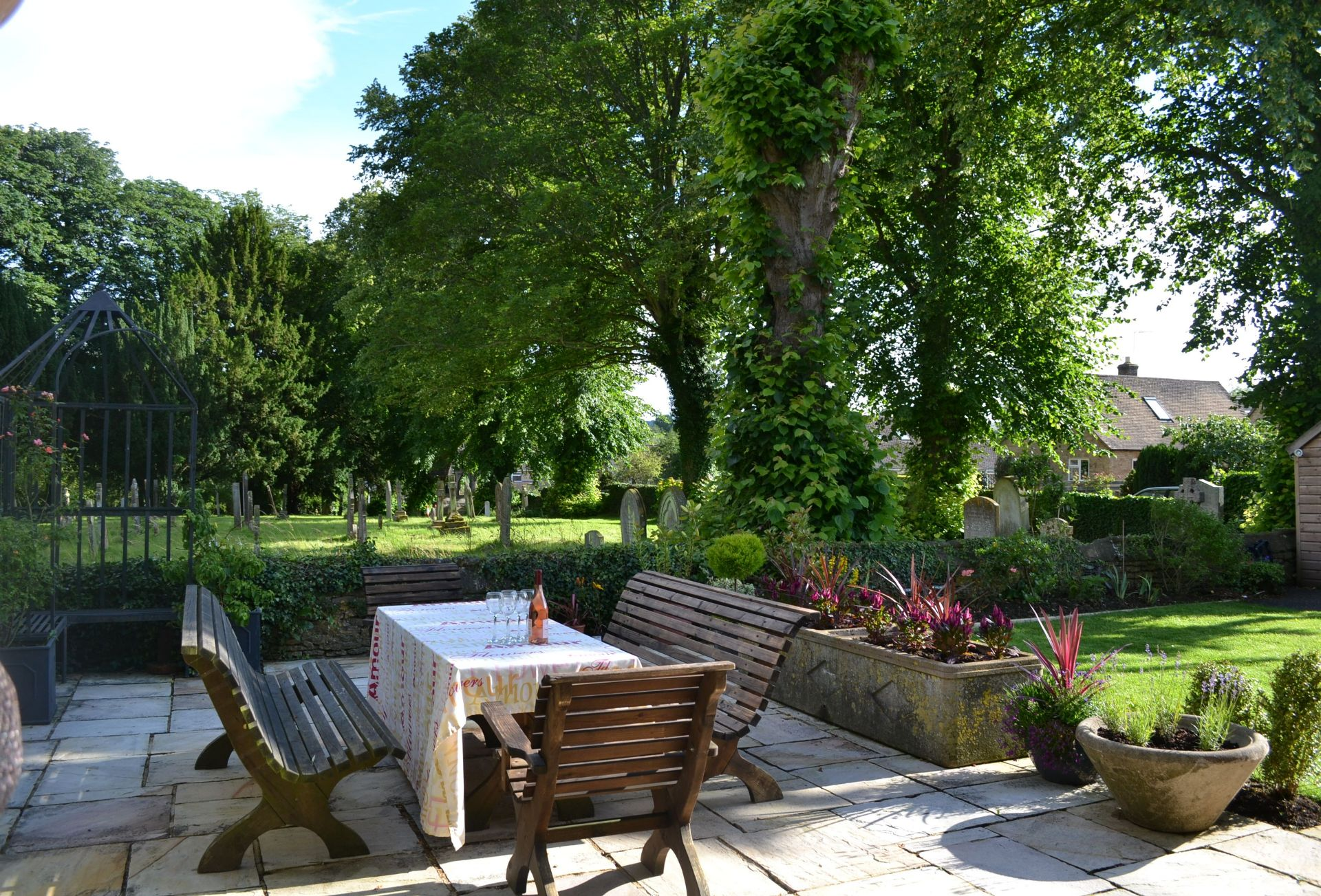 The garden includes a lawn and terrace area with a table and seating for six