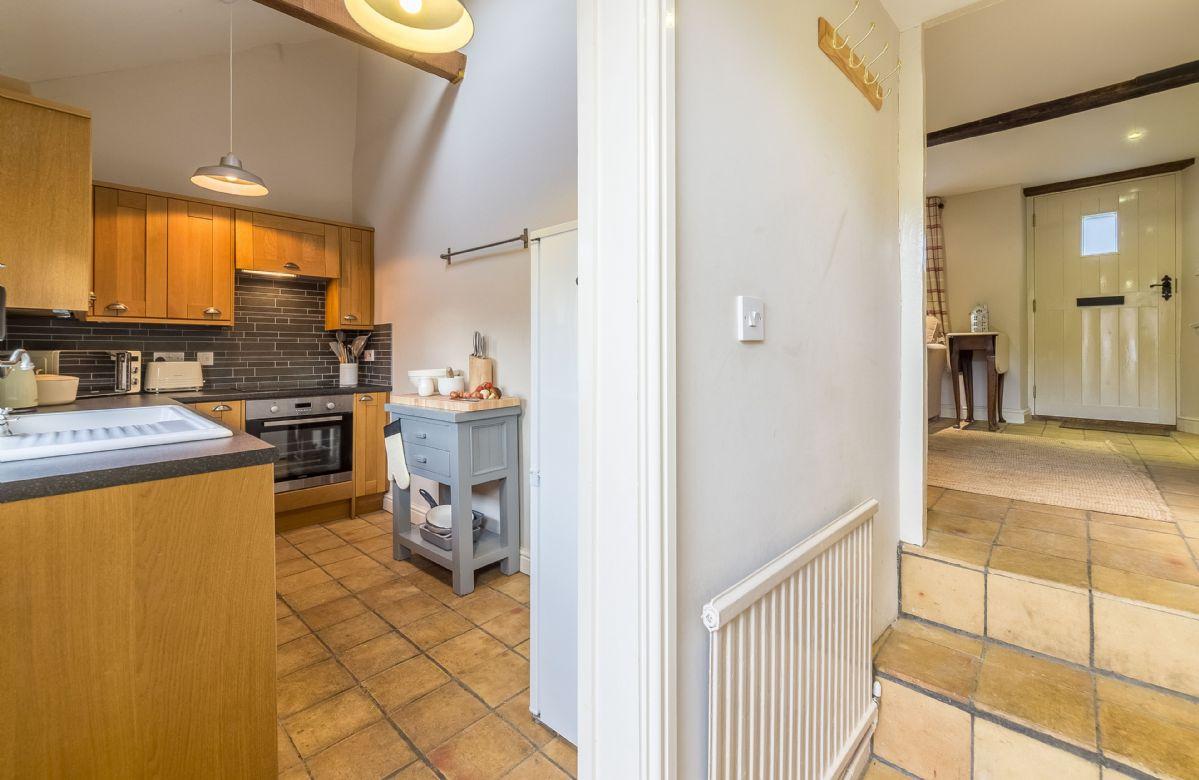 Ground floor:  Steps leading into kitchen with handmade floor tiles