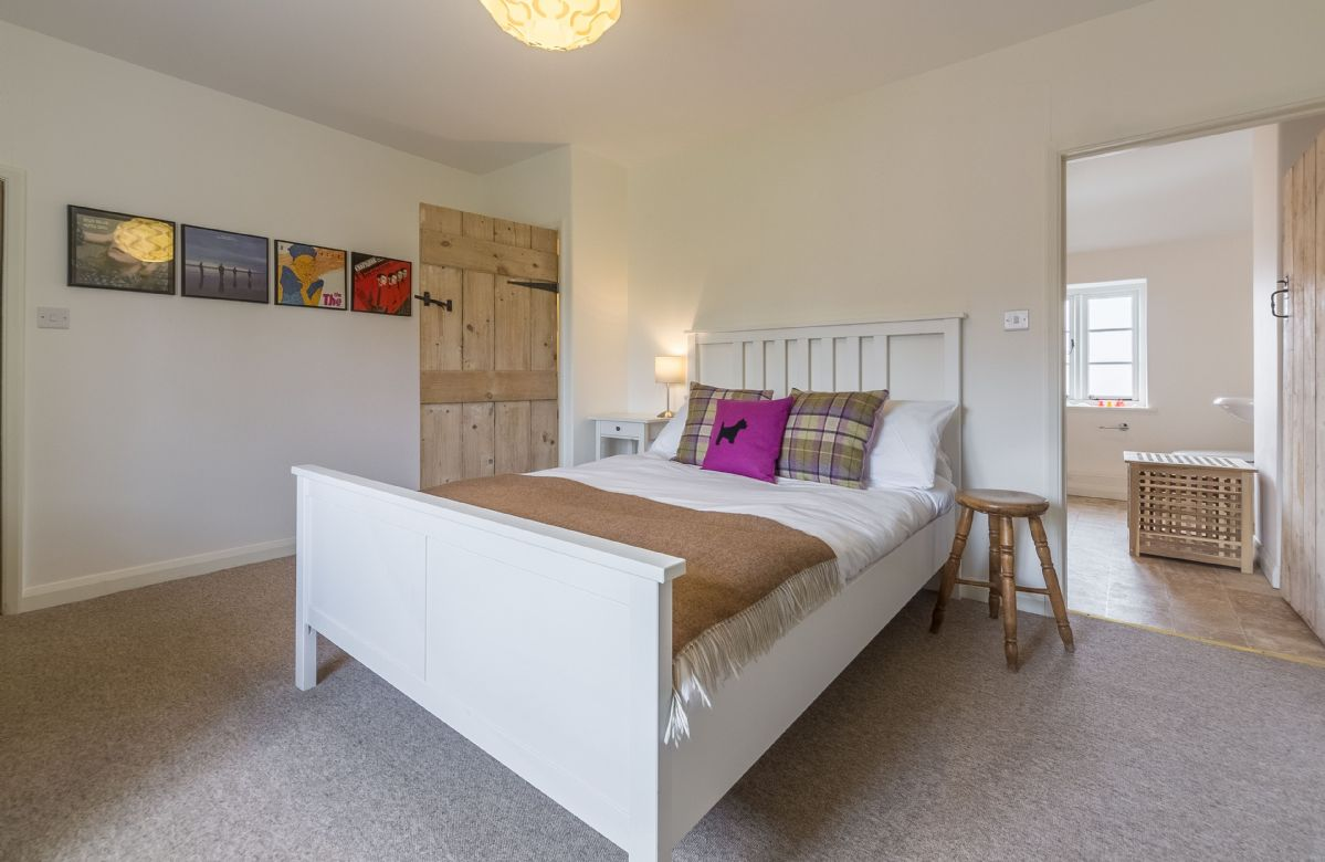 First floor: Master bedroom with double bed and views across open countryside