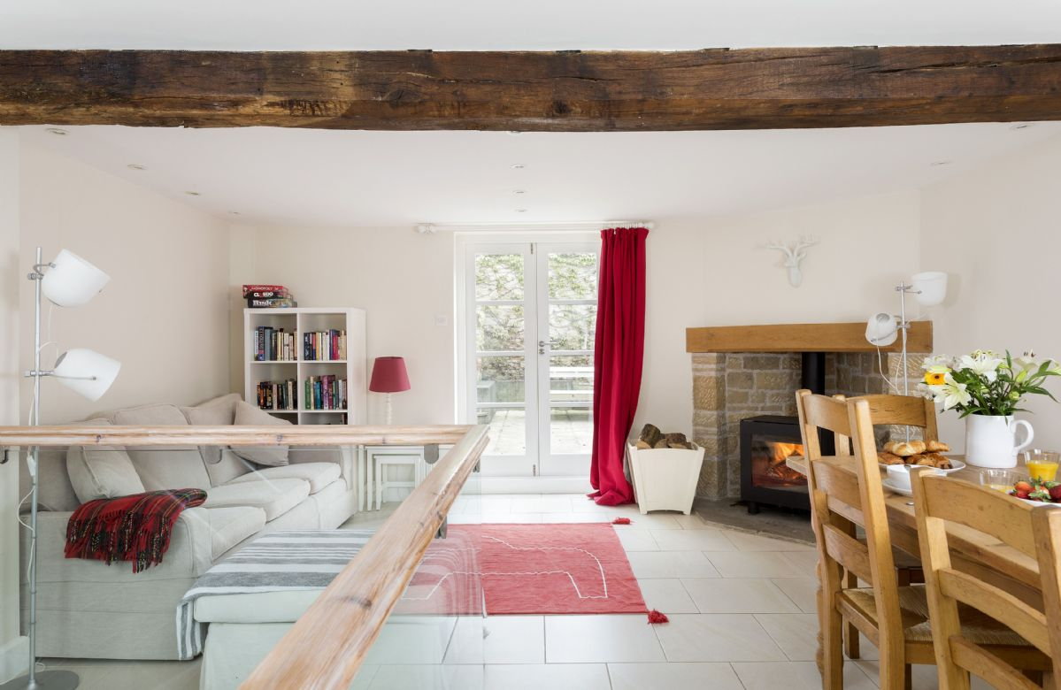Ground floor: Spacious dining  and seating area with wood burning stove. Stairs leading to lower ground sitting room