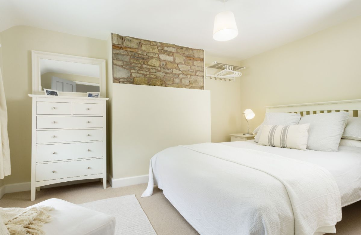 First floor:  Bedroom one with king size bed light and airy with exposed stone work.