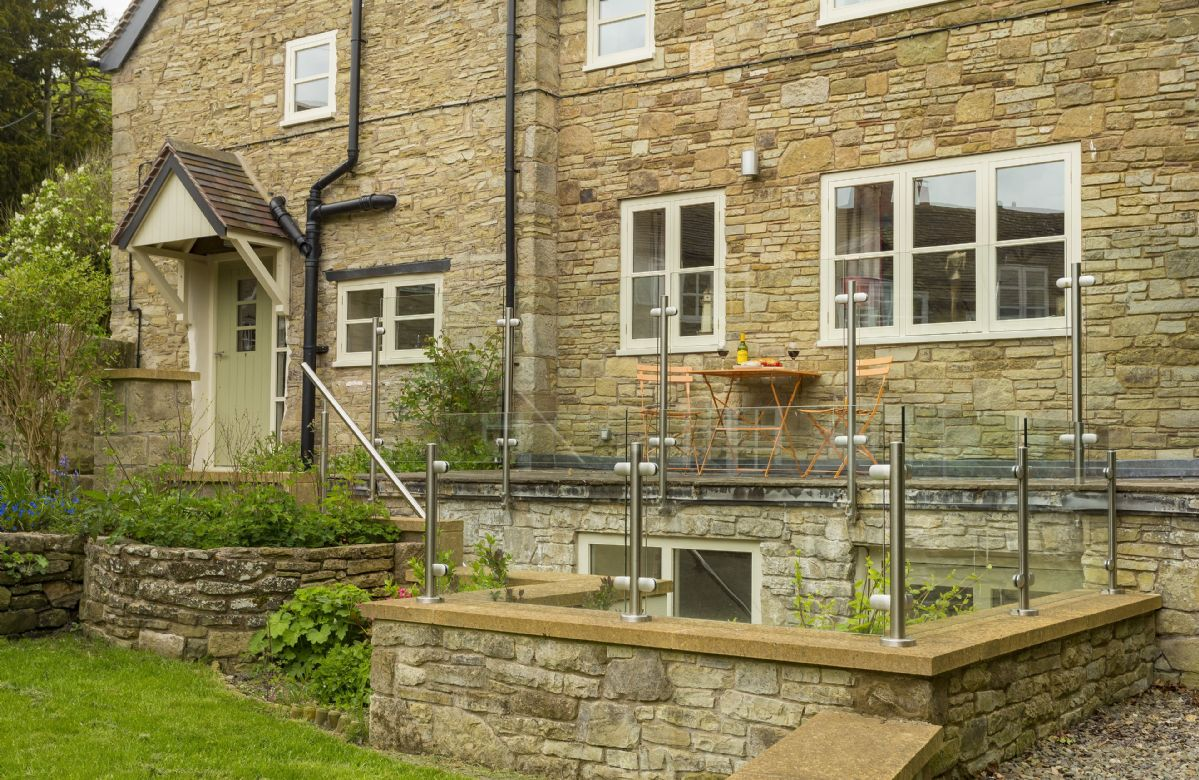 Front terrace with steps leading to lower enclosed dining area with gas barbecue