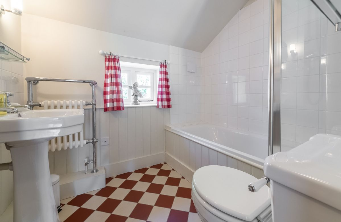 Ground floor: Bathroom with traditional style fittings and bath with overhead shower