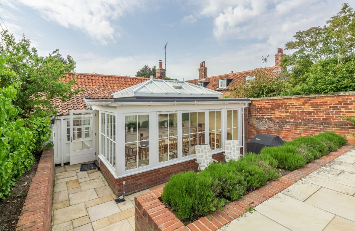 To the rear of Myrtle Cottage is the large conservatory dining room which opens on to a paved, fully enclosed garden with raised terrace