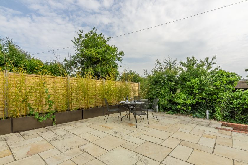 To the rear of Myrtle Cottage is a paved, fully enclosed garden with raised terrace