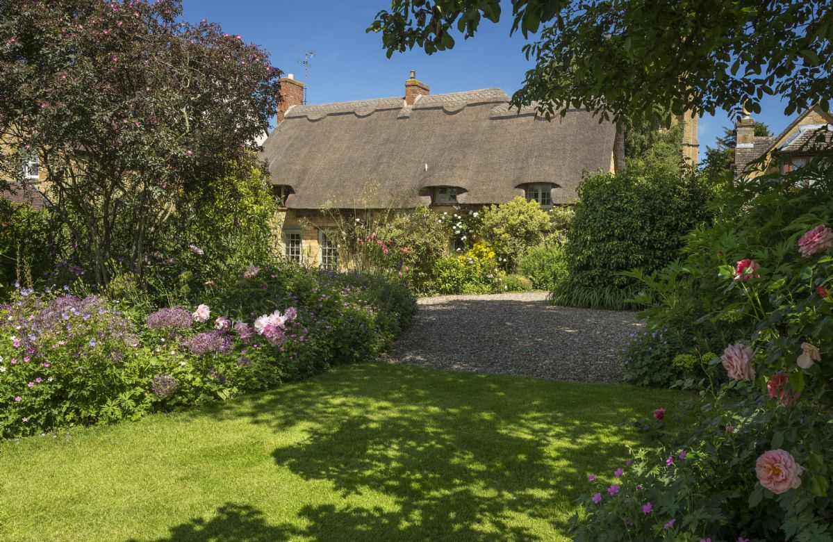 To the rear of the cottage are fully enclosed gardens, partially laid to lawn with borders packed with colour and variety