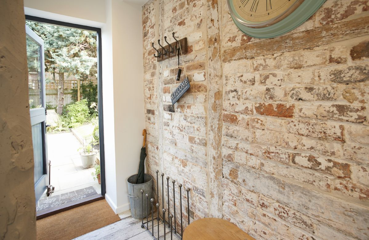 Ground floor:  Entrance with exposed stone wall.