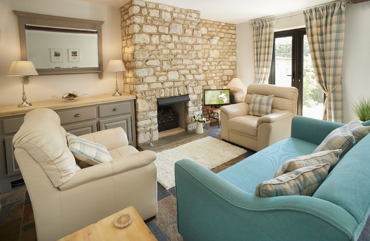 Ground floor: Relax in the sitting room with exposed stone wall.