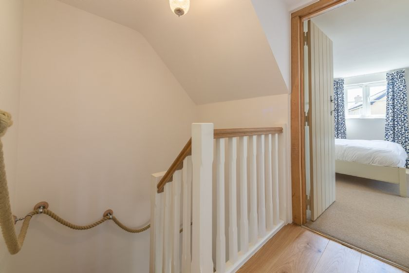First floor: Top of stairs with entrance to master bedroom