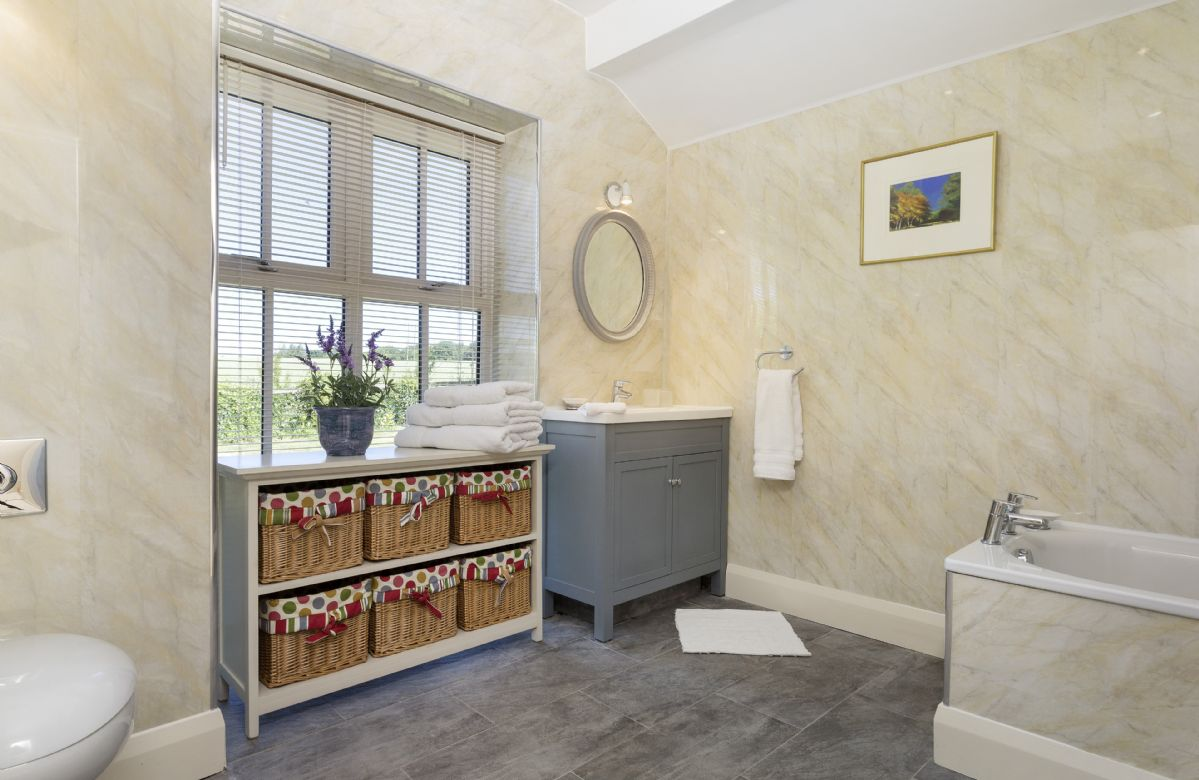 Ground floor: Large en-suite bathroom with vanity unit and high windows