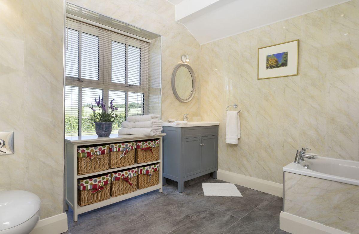 Ground floor: Large en-suite bathroom with vanity unit and high windows