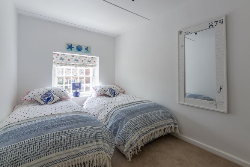 First floor: Bedroom three has two single beds and views to the rear garden