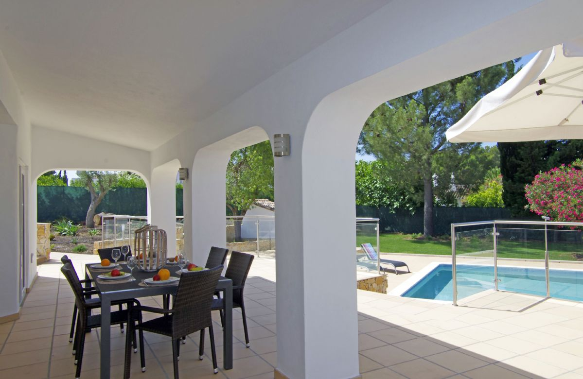 Covered terrace with table and chairs overlooking the swimming pool