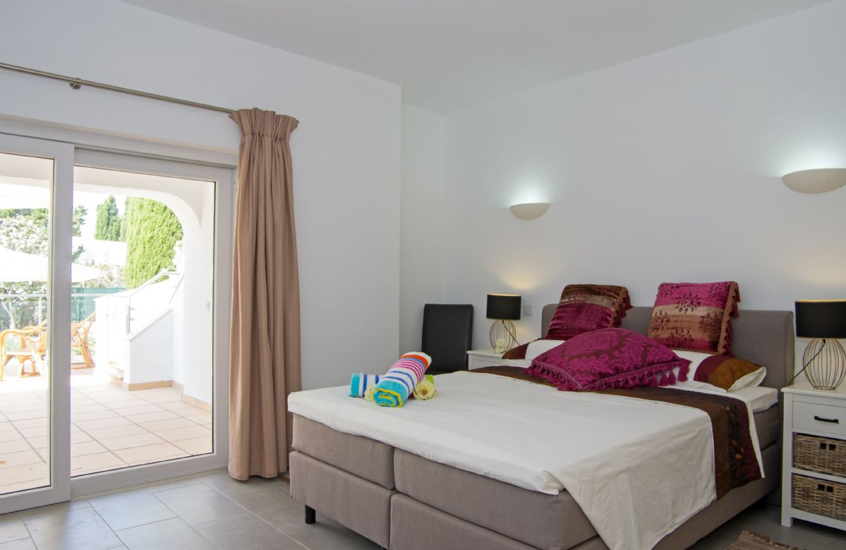 Ground floor: Master bedroom with en-suite shower room and doors to the covered terrace