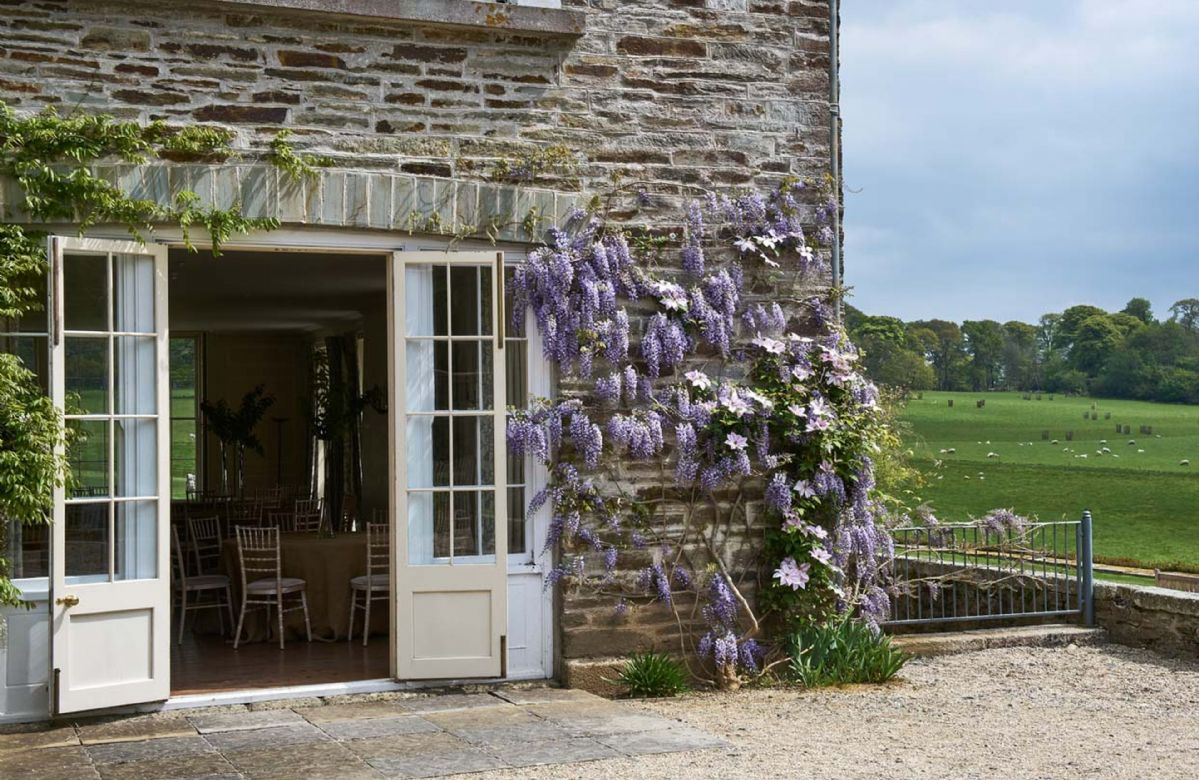 Original stone walls and beautiful Wysteria alongside views of extensive gardens