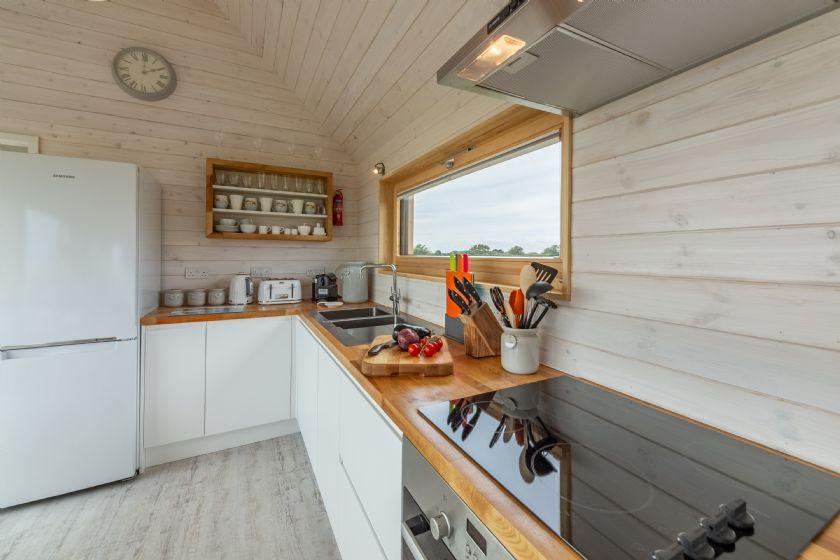 Ground floor: Open-plan kitchen and sitting room with door opening onto decked terrace with outside furniture